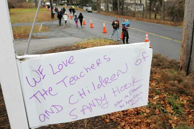 Mourners make their way to the Sandy Hook Elementary School memorial Sunday Dec. 16, 2012, in Newtown Conn. Twenty-seven people including 20 students were gunned down on Friday. Photo: Will Waldron, Hearst Newspapers/Will Waldron / The News-Times