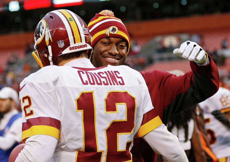 Injured Washington Redskins quarterback Robert Griffin III, right, hugs Kirk Cousins (12) after a 38-21 win over the Cleveland Browns in an NFL football game in Cleveland, Sunday, Dec. 16, 2012. Cousins passed for 329 yards and two touchdowns filling in for Griffin. (AP Photo/Rick Osentoski) Photo: Rick Osentoski