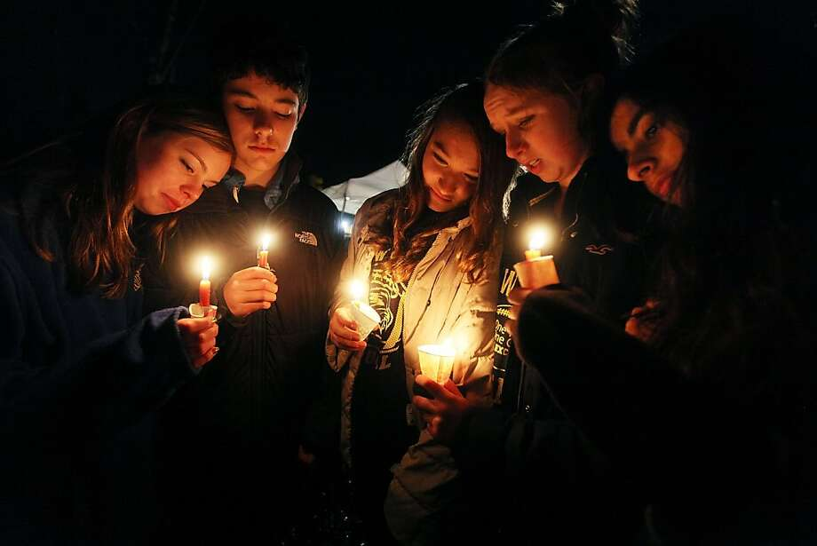 NEWTOWN, CT - DECEMBER 16:  (L to R) Newtown residents Claire Swanson, Ian Fuchs, Kate Suba, Jaden Albrecht, Simran Chand hold candles at a memorial for victims on the first Sunday following the mass shooting at Sandy Hook Elementary School on December 16, 2012 in Newtown, Connecticut. U.S. President Barack Obama visited the grief stricken town today.  (Photo by Mario Tama/Getty Images) Photo: Mario Tama, Getty Images