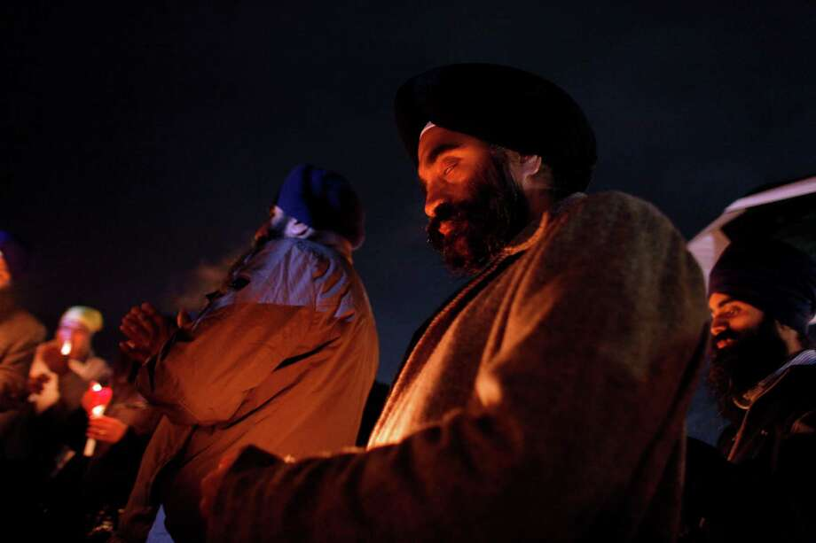 C.J. Singh, center, and other members of the Sikh  community hold a candlelight vigil outside Newtown High School before an interfaith vigil with President Barack Obama, Sunday, Dec. 16, 2012, in Newtown, Conn.  A gunman walked into Sandy Hook Elementary School in Newtown Friday and opened fire, killing 26 people, including 20 children. (AP Photo/Jason DeCrow) Photo: AP