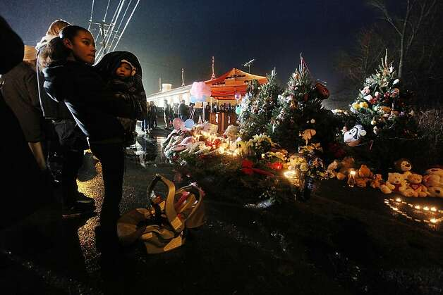 NEWTOWN, CT - DECEMBER 16:  Isabel Lebron holds son Izaiah Taylor at a memorial with donated Christmas trees honoring victims near the school on the first Sunday following the mass shooting at Sandy Hook Elementary School on December 16, 2012 in Newtown, Connecticut. U.S. President Barack Obama visited the grief stricken town today.  (Photo by Mario Tama/Getty Images) Photo: Mario Tama, Getty Images