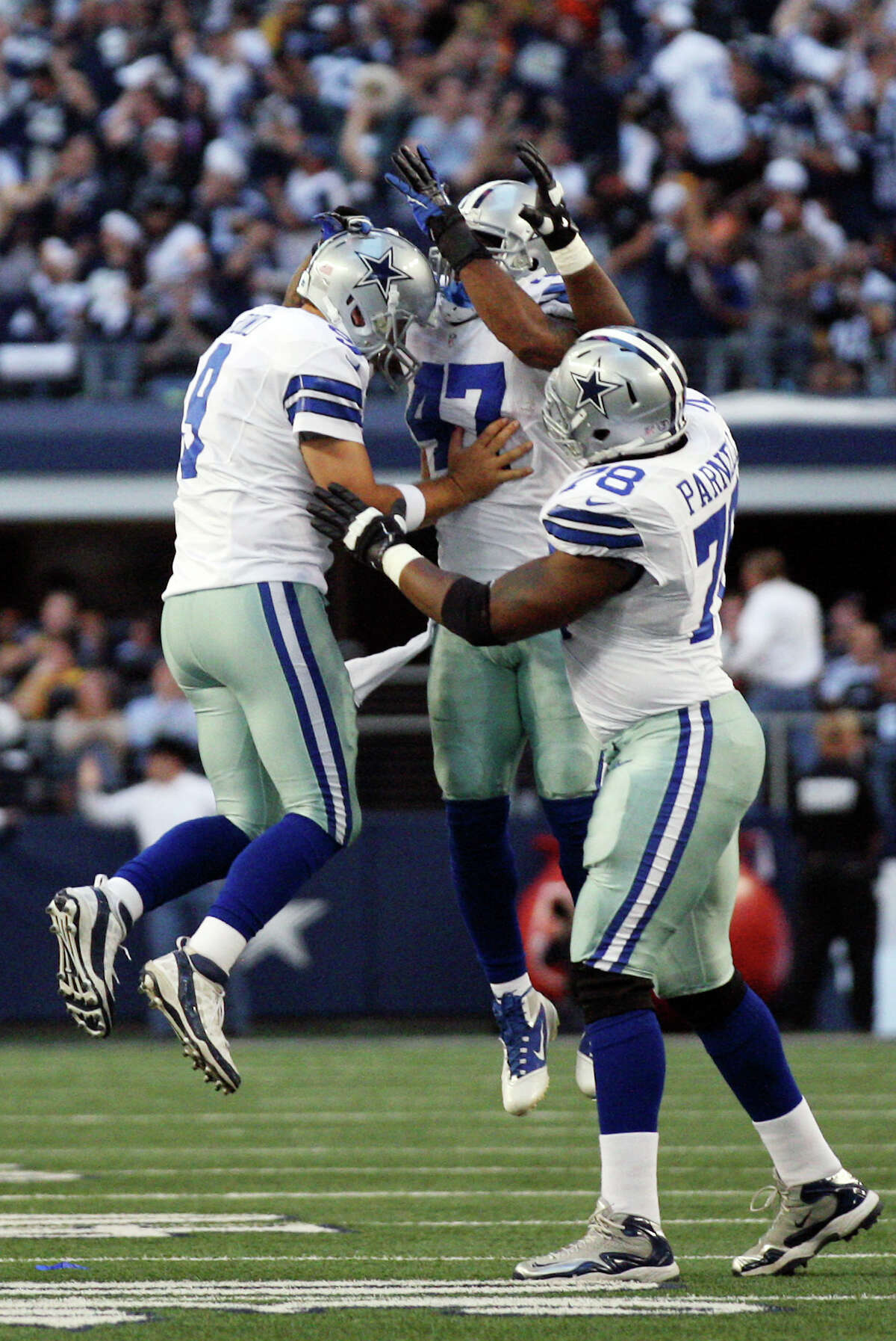 Dallas Cowboys' quarterback Tony Romo, left, celebrates with Lawrence Vickers, (47) and Jermey Parnell, (78), after a touchdown pass to Jason Witten in the second quarter agaisnt the Pittsburgh Steelers at Cowboys Stadium in Arlington, Texas, Sunday, Dec. 16, 2012.