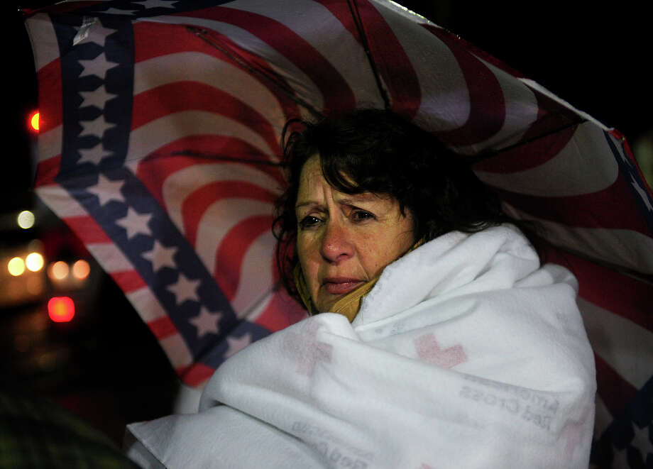 Newtown schools bus driver Nancy Liliberte, of Shelton, stays warm with a Red Cross blanket outside Newtown High School where President Barack Obama spoke on Sunday, December 16, 2012. Photo: Brian A. Pounds / Connecticut Post