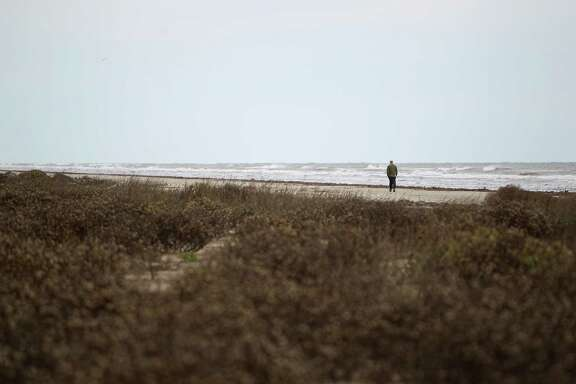 Kelly Chapman, from Chicago, strolls along the beach Monday at Galveston Island State Park where the sand dunes are protected by plants and grasses.
