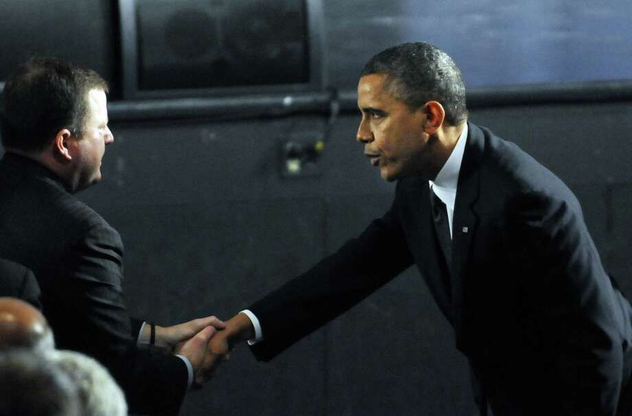 President Barack Obama greets State Senate Minority Leader John McKinney, R-Fairfield, on his arrival, before the start of an interfaith vigil for the victims of the Sandy Hook Elementary School shooting inside the Newtown High School auditorium in Newtown, Conn., Sunday night, Dec. 16, 2012. A gunman walked into the elementary school Friday and opened fire, killing 26 people, including 20 children. (AP Photo/The Hartford Courant, Stephen Dunn, Pool) Photo: AP