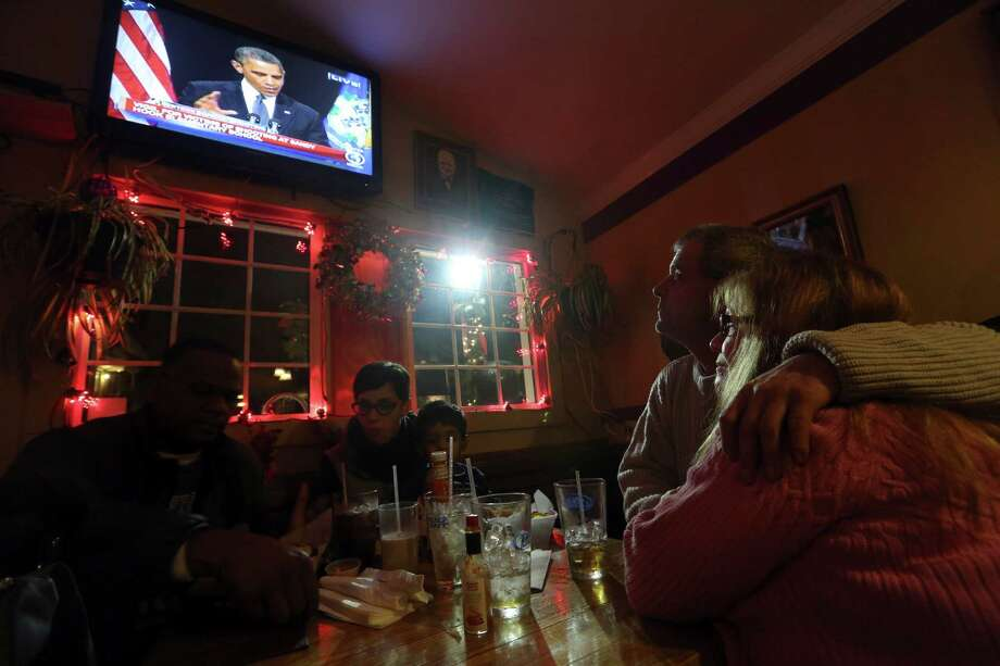 Julie LaPak, right, and Scott Emslie, of Newton, Conn., watch President Obama delver his speech at the Iron Bridge restaurant, Sunday, Dec. 16, 2012 in Newtown, Conn. (AP Photo/Mary Altaffer) Photo: AP