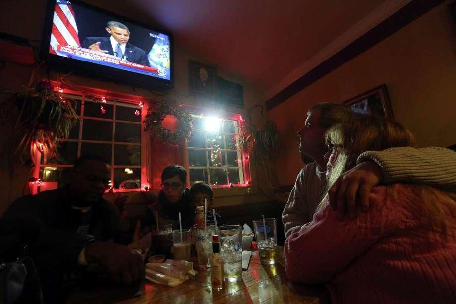 Julie LaPak, right, and Scott Emslie, of Newton, Conn., watch President Obama delver his speech at the Iron Bridge restaurant, Sunday, Dec. 16, 2012 in Newtown, Conn. (AP Photo/Mary Altaffer) Photo: AP