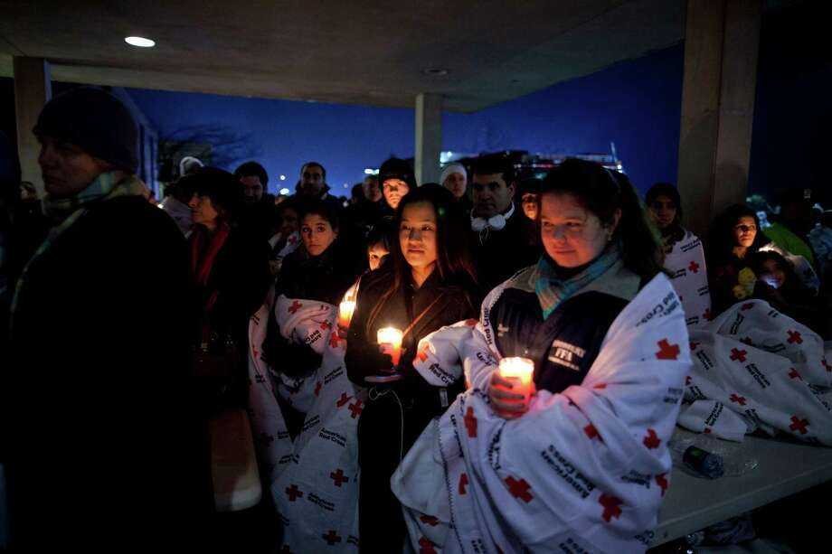 Residents hold a candlelight vigil outside Newtown High School after President Barack Obama delivered remarks at an interfaith vigil for the victims of the Sandy Hook Elementary School shooting on Sunday, Dec. 16, 2012, at Newtown High School in Newtown, Conn. A gunman walked into the elementary school Friday and opened fire, killing 26 people, including 20 children. (AP Photo/ Evan Vucci) Photo: AP