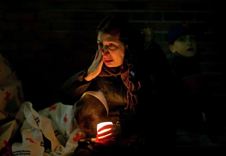 A mourner weeps while listening to President Barack Obama speak on a loudspeaker while sitting outside a memorial at Newtown High School for the victims of the Sandy Hook Elementary School shooting, Sunday, Dec. 16, 2012, in Newtown, Conn. (AP Photo/David Goldman) Photo: AP