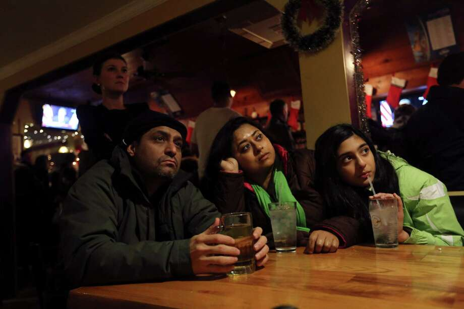 Surendra Khera, left, Manjaree Daw, center and Indira Khera, of Simsbury, Conn., watch President Obama deliver his speech at the Iron Bridge restaurant, Sunday, Dec. 16, 2012 in Newtown, Conn. The president spoke during an interfaith vigil for the victims of the Sandy Hook Elementary School shooting. A gunman walked into the elementary school Friday and opened fire, killing 26 people, including 20 children. (AP Photo/Mary Altaffer) Photo: AP