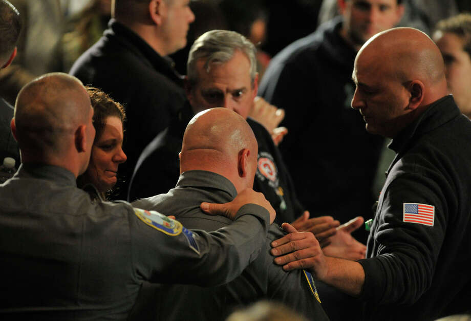 People rise, applaud and console the first responders as they enter the room during an interfaith vigil for the families and residents affected by the Sandy Hook Elementary School shooting at Newtown High School in Newtown, Conn., on Sunday, Dec. 16, 2012. Photo: Jason Rearick / The News-Times