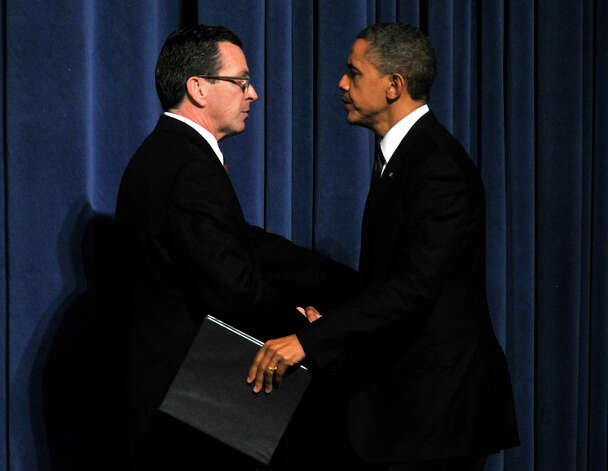 President Barack Obama greets Connecticut Gov. Dannel P. Malloy during an interfaith vigil for the families and residents affected by the Sandy Hook Elementary School shooting at Newtown High School in Newtown, Conn., on Sunday, Dec. 16, 2012. Photo: Jason Rearick