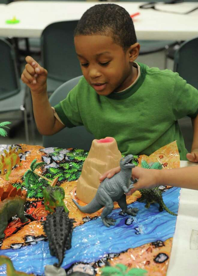 Five-year-old Robert Scott plays with dinosaurs during the after school program at Trinity Alliance in Albany, NY Thursday Dec. 6, 2012. (Michael P. Farrell/Times Union) Photo: Michael P. Farrell