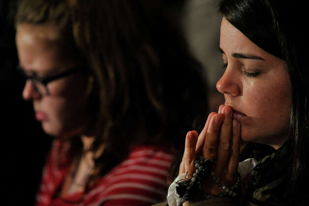 People pray during an interfaith vigil for the families and residents affected by the Sandy Hook Elementary School shooting at Newtown High School in Newtown, Conn., on Sunday, Dec. 16, 2012. Photo: Jason Rearick