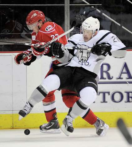 Charlotte Checkers' Drayson Bowman, left, and San Antonio Rampage's Jon Rheault collide during an AHL hockey game, Sunday, Dec. 16, 2012, in San Antonio. Charlotte won 2-1. Photo: Darren Abate, Darren Abate/pressphotointl.com / Darren Abate/pressphotointl.com