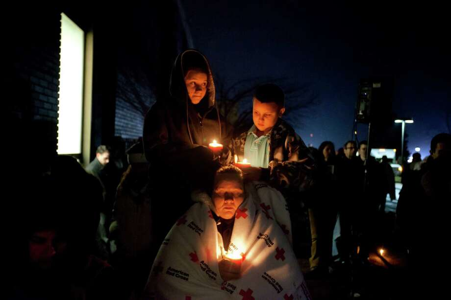 Sharon Bertrand, center, listens with her daughter Daysha, 13, left, and son Juan, all of Waterbury, Conn., to a memorial service over a loudspeaker outside Newtown High School for the victims of the Sandy Hook Elementary School shooting, Sunday, Dec. 16, 2012, in Newtown, Conn. (AP Photo/David Goldman) Photo: AP