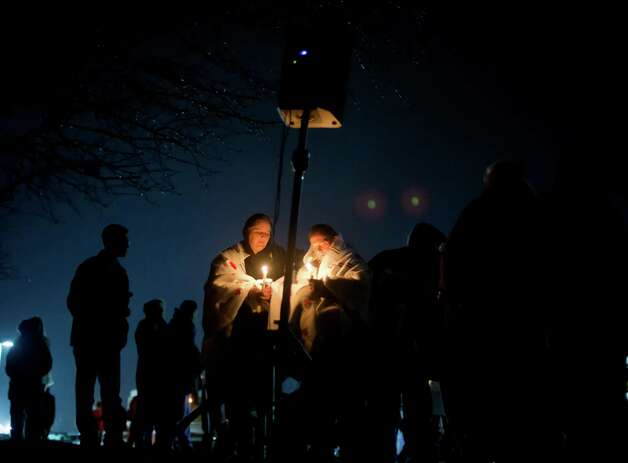 Mourners listen to a memorial service over a loudspeaker outside Newtown High School for the victims of the Sandy Hook Elementary School shooting, Sunday, Dec. 16, 2012, in Newtown, Conn. A gunman walked into the elementary school Friday and opened fire, killing 26 people, including 20 children. (AP Photo/David Goldman) Photo: AP