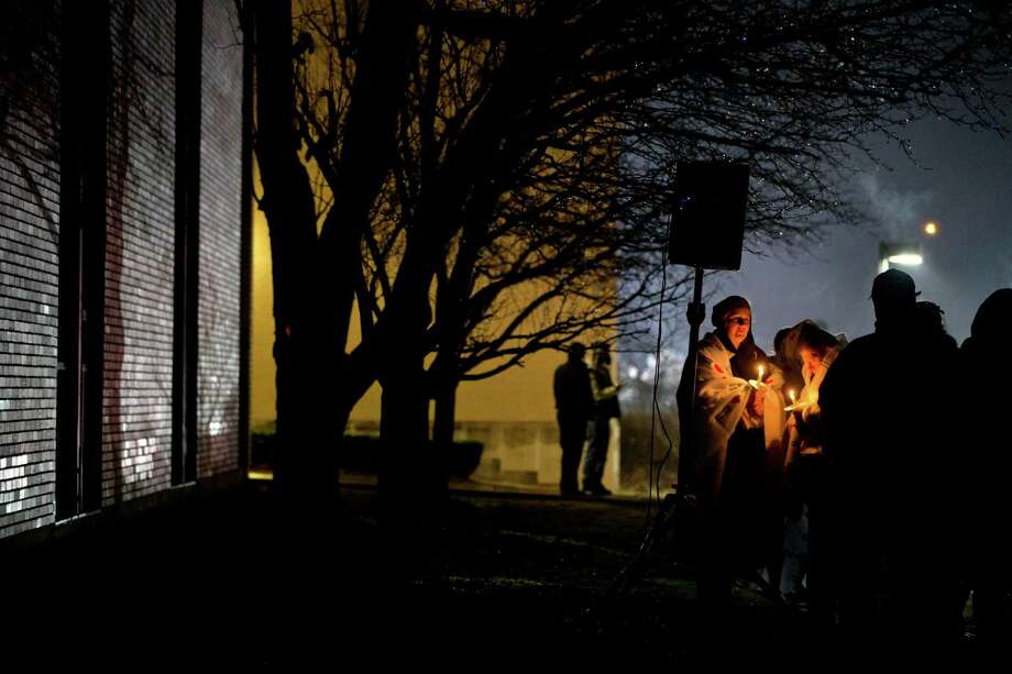 Mourners listen to a memorial service over a loudspeaker outside Newtown High School for the victims of the Sandy Hook Elementary School shooting, Sunday, Dec. 16, 2012, in Newtown, Conn. (AP Photo/David Goldman) Photo: AP