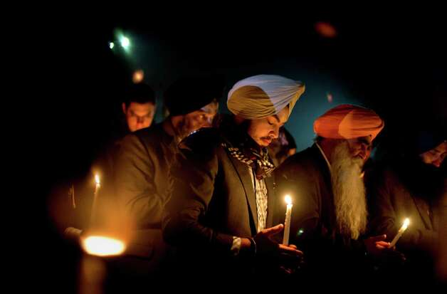 Varinder Singh, of the Queens borough of New York, joins a group of Sikhs from around the Northeastern U.S., in a moment of prayer as a memorial service is broadcast over a loudspeaker outside Newtown High School for the victims of the Sandy Hook Elementary School shooting, Sunday, Dec. 16, 2012, in Newtown, Conn. (AP Photo/David Goldman) Photo: AP