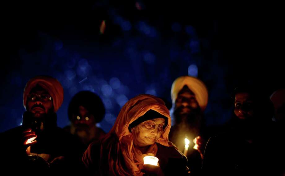 Surjit Kaur Gill, of Worcester, Mass., joins a group of Sikhs from around the Northeastern U.S., in a moment of prayer as a memorial service is broadcast over a loudspeaker outside Newtown High School for the victims of the Sandy Hook Elementary School shooting, Sunday, Dec. 16, 2012, in Newtown, Conn. (AP Photo/David Goldman) Photo: AP
