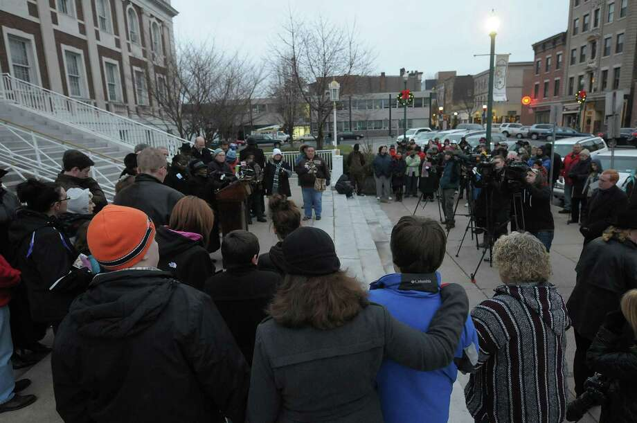 People gather for a candlelight prayer vigil outside of city hall on Sunday, Dec. 16, 2012 in Schenectady, NY.  The vigil was held to show support for the families and community members of Newtown, CT.  The vigil was organized by the Hamilton Hill Neighborhood Association.  (Paul Buckowski / Times Union) Photo: Paul Buckowski