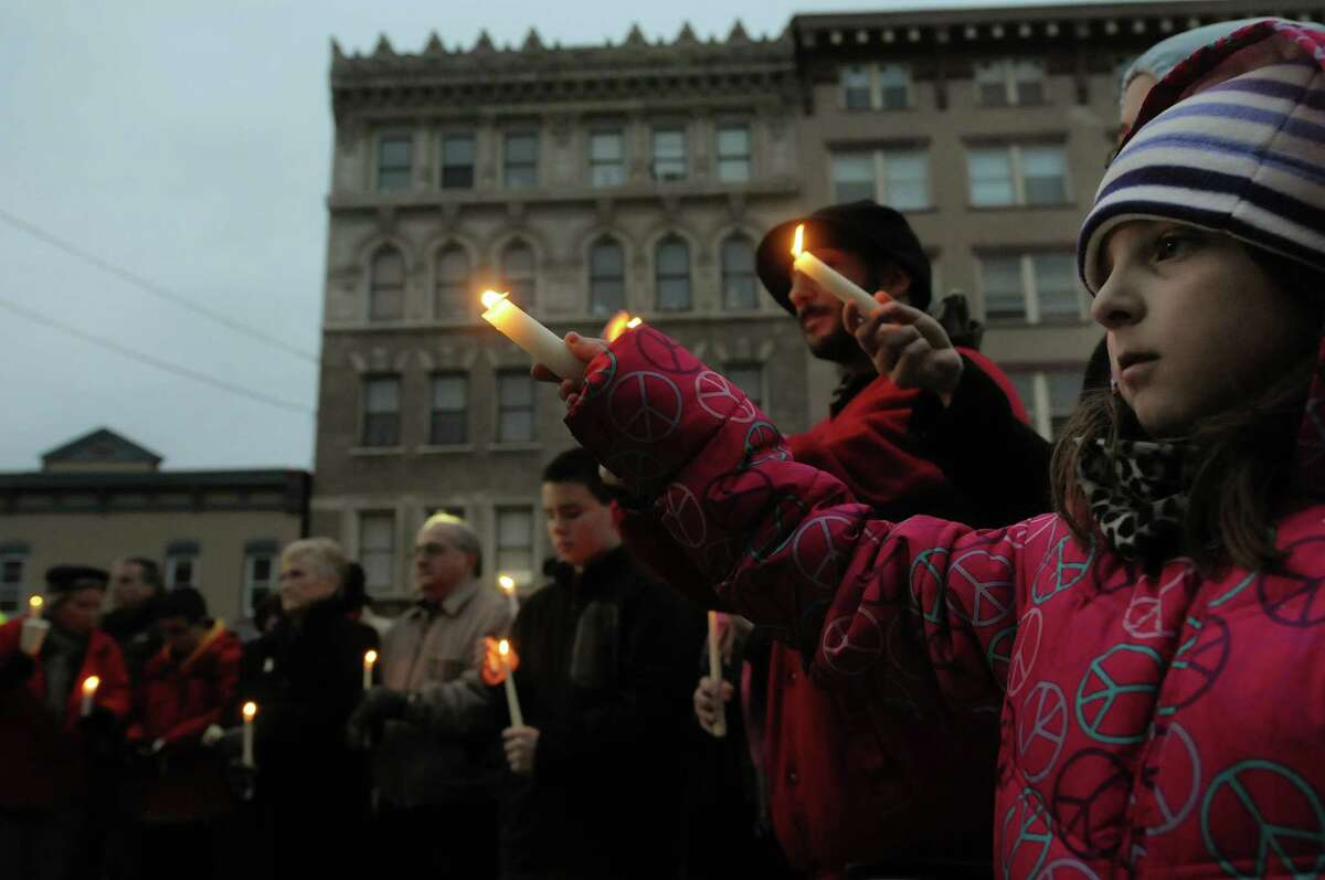 Maria Silverio, 8, from Schenectady takes part in a candlelight prayer vigil outside of city hall on Sunday, Dec. 16, 2012 in Schenectady, NY. The vigil was held to show support for the families and community members of Newtown, CT. The vigil was organized by the Hamilton Hill Neighborhood Association. (Paul Buckowski / Times Union)