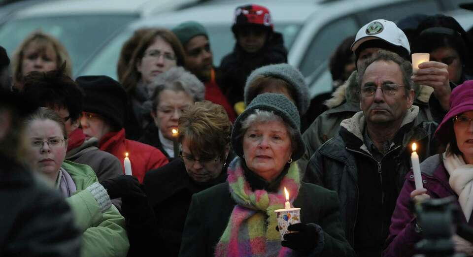 People hold candles as they take part in a candlelight prayer vigil outside of city hall on Sunday,