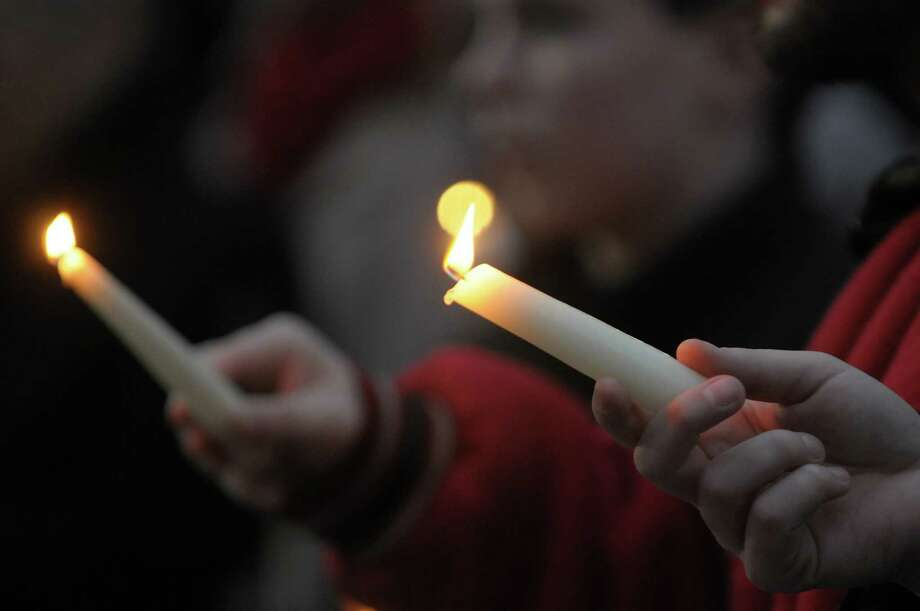 People hold candles as they take part in a candlelight prayer vigil outside of city hall on Sunday, Dec. 16, 2012 in Schenectady, NY.  The vigil was held to show support for the families and community members of Newtown, CT.  The vigil was organized by the Hamilton Hill Neighborhood Association.  (Paul Buckowski / Times Union) Photo: Paul Buckowski