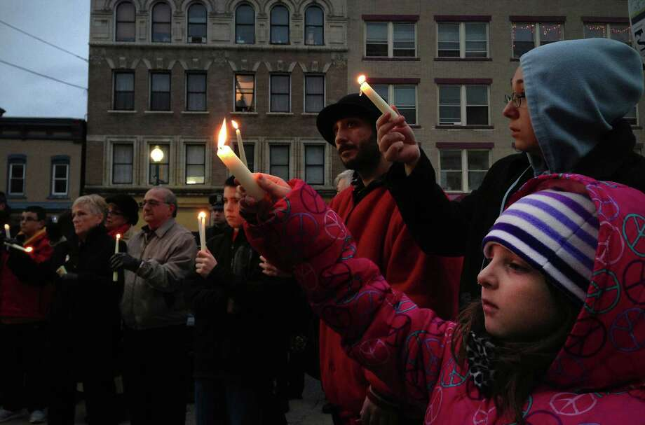 Maria Silverio, 8, from Schenectady holds her candle up as she takes part in a candlelight prayer vigil outside of city hall on Sunday, Dec. 16, 2012 in Schenectady, NY.  The vigil was held to show support for the families and community members of Newtown, CT.  The vigil was organized by the Hamilton Hill Neighborhood Association.  (Paul Buckowski / Times Union) Photo: Paul Buckowski