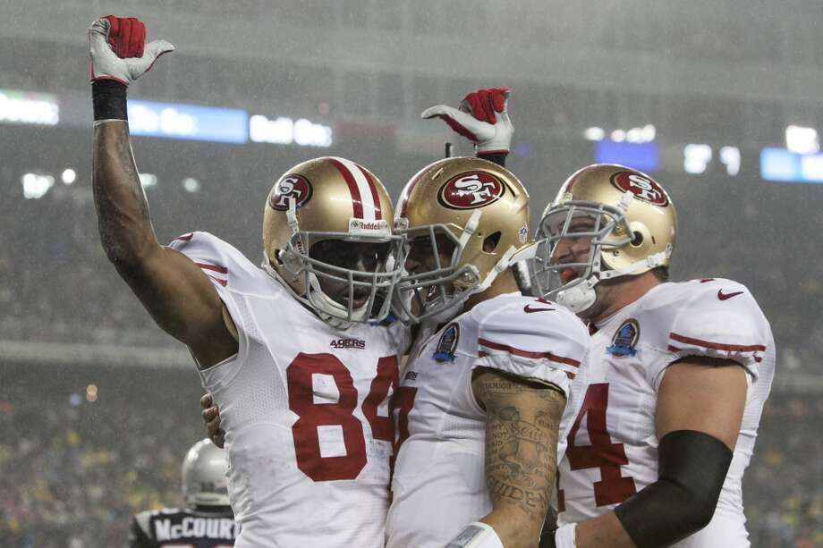 49ers wide receiver Randy Moss, left, celebrates his first quarter touchdown against the Patriots with quarterback Colin Kaepernick, center, and tackle Joe Staley in their game at Gillette Stadium on Dec. 16, 2012. (Kelvin Ma / Special to the Chronicle)