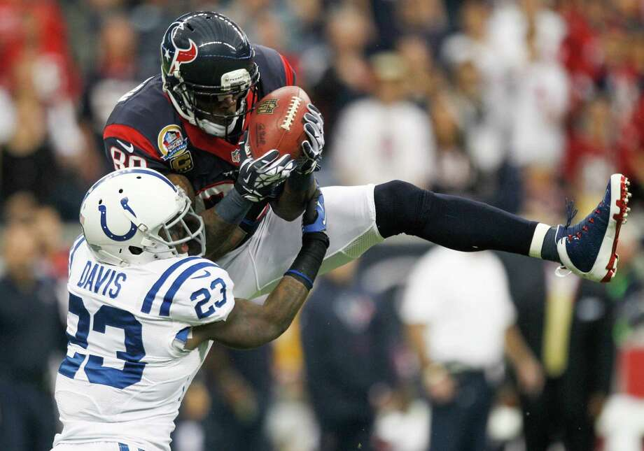 Texans wide receiver Andre Johnson makes a midfield catch over Colts cornerback Vontae Davis during the first quarter. Photo: Brett Coomer, Houston Chronicle / © 2012  Houston Chronicle