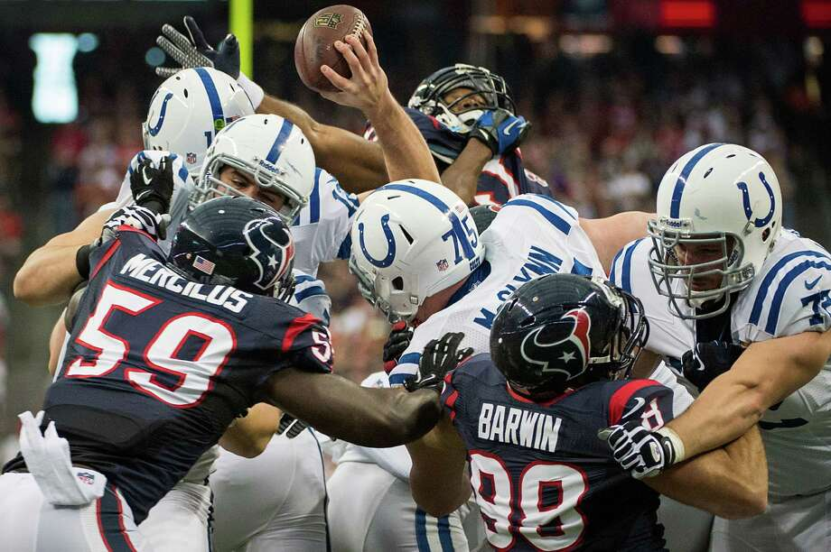 The pocket collapses around Colts quarterback Andrew Luck as tries to get off a pass against Texans nose tackle Earl Mitchell (92), linebacker Whitney Mercilus (59) and linebacker Connor Barwin (98) during the first quarter. Photo: Smiley N. Pool, Houston Chronicle / © 2012  Houston Chronicle
