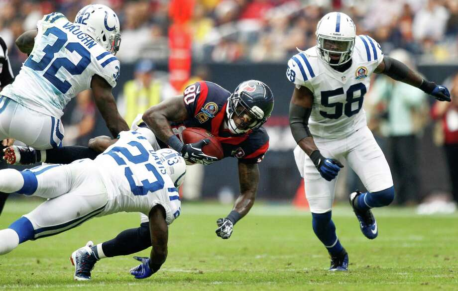 Texans wide receiver Andre Johnson (80) makes a catch between Colts defensive backs Cassius Vaughn (32), Vontae Davis (23) and Moise Fokou (58) during the second quarter. Photo: Brett Coomer, Houston Chronicle / © 2012  Houston Chronicle