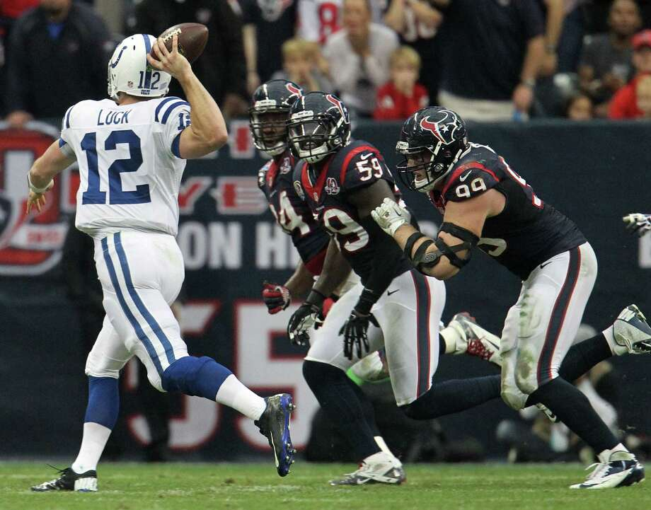 Colts quarterback Andrew Luck (12) throws on the run as Houston Texans defensive end J.J. Watt (99), outside linebacker Whitney Mercilus (59) and defensive end Antonio Smith (94) provide pressure during the second quarter. Photo: Karen Warren, Houston Chronicle / © 2012 Houston Chronicle