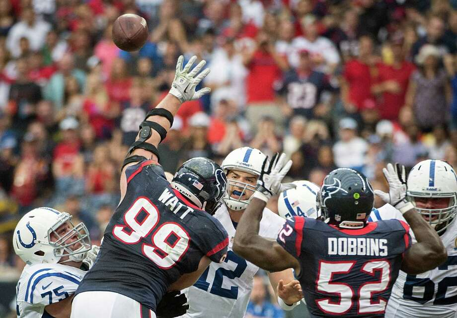 Colts quarterback Andrew Luck (12) gets off a pass as Texans defensive end J.J. Watt (99) and linebacker Tim Dobbins (52) apply pressure. Photo: Smiley N. Pool, Houston Chronicle / © 2012  Houston Chronicle