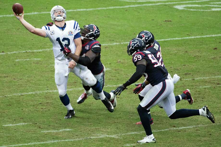 Colts quarterback Andrew Luck (12) gets off a pass as he is hit by Houston Texans defensive end Antonio Smith (94). Luck was flagged for intentional grounding on the play. Photo: Smiley N. Pool, Houston Chronicle / © 2012  Houston Chronicle