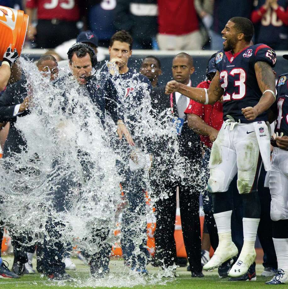 Texans head coach Gary Kubiak is doused with a bucket of water at the end of the fourth quarter as running back Arian Foster (23) celebrates. Photo: Brett Coomer, Houston Chronicle / © 2012  Houston Chronicle