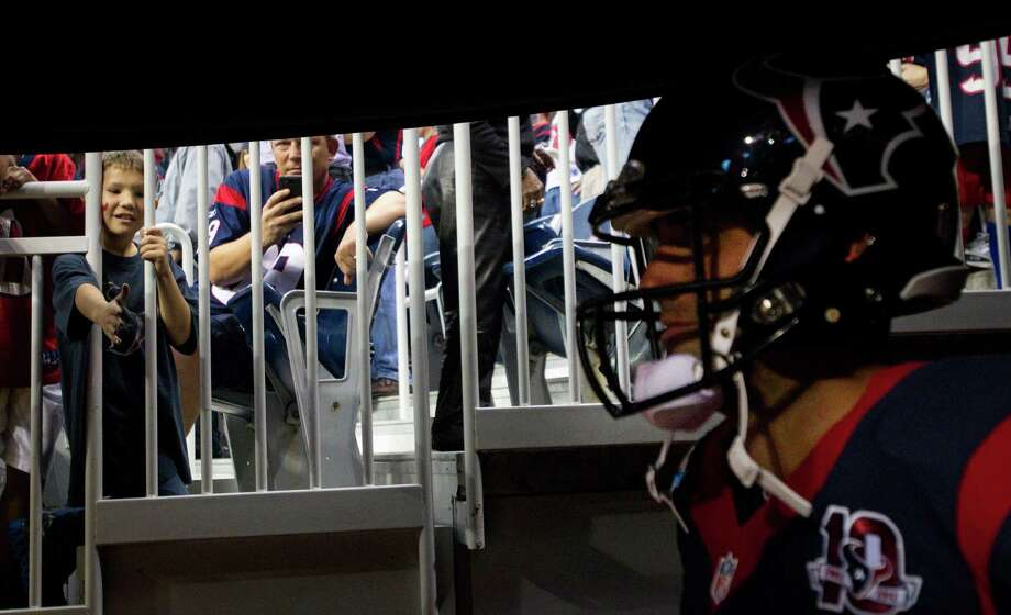 Texans fans look through a railing to see quarterback Matt Schaub as he waits to be introduced before the Texans game against the Indianapolis Colts at Reliant Stadium. Photo: Brett Coomer, Houston Chronicle / © 2012  Houston Chronicle