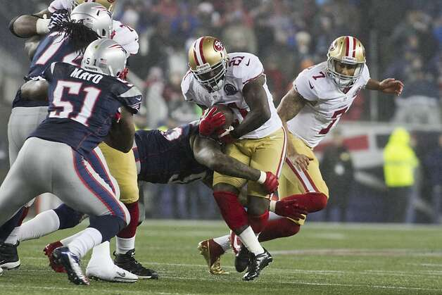 49ers running back Frank Gore gets tackled by Patriots linebacker Brandon Spikes in the first quarter in their game at Gillette Stadium on Dec. 16, 2012. Photo: Kelvin Ma, Special To The Chronicle