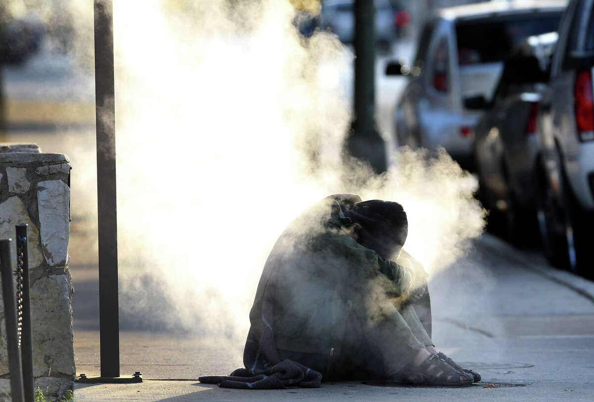 A man who appeared to be homeless tries to warm himself on a steaming grate on Market street near Alamo Tuesaday morning December 11, 2012. A police officer appeared moments later and told the man to leave. This morning's temperatures were in the lower 30s and tomorrow's low is predicted to be 34 degrees.