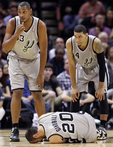 San Antonio Spurs' Boris Diaw and Danny Green look on as Manu Ginobili lies on the floor after being injured during first half action against the Boston Celtics Saturday Dec. 15, 2012 at the AT&T Center. Photo: Edward A. Ornelas, San Antonio Express-News / © 2012 San Antonio Express-News