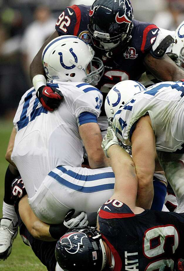 Texans defensive end J.J. Watt (99) and nose tackle Earl Mitchell (92) sack Colts quarterback Andrew Luck (12) during the fourth quarter. Photo: Brett Coomer, Houston Chronicle / © 2012  Houston Chronicle
