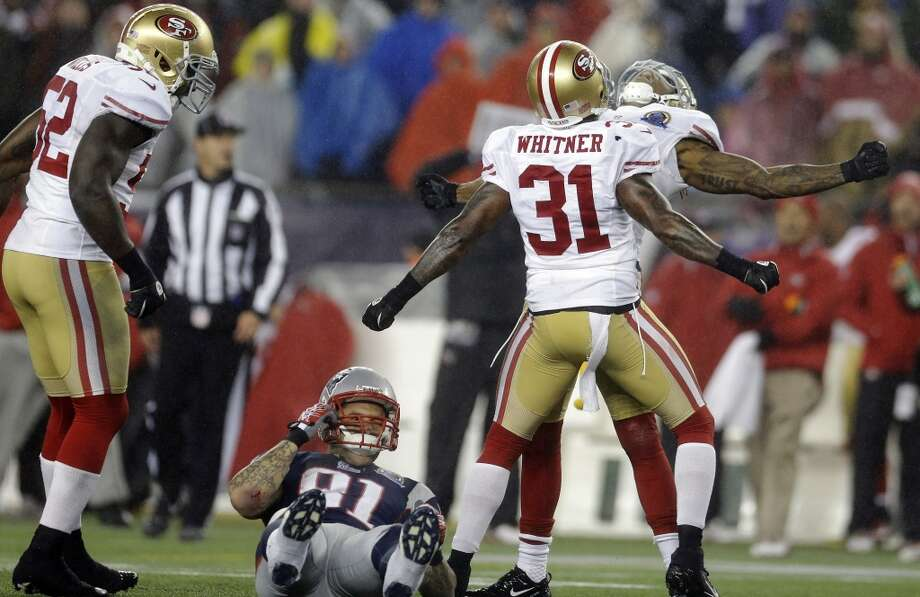 San Francisco 49ers safeties Donte Whitner (31) and Dashon Goldson, right rear, react in the third quarter of an NFL football game as New England Patriots tight end Aaron Hernandez (81) lies on the turf in Foxborough, Mass., Sunday, Dec. 16, 2012. At left is 49ers inside linebacker Patrick Willis (52).  (Elise Amendola / Associated Press)