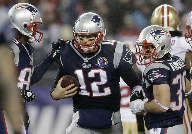 New England Patriots quarterback Tom Brady (12) celebrates his touchdown against the San Francisco 49ers with wide receiver Brandon Lloyd, left, and running back Danny Woodhead, right, in the fourth quarter of an NFL football game in Foxborough, Mass., Sunday, Dec. 16, 2012. (AP Photo/Elise Amendola) Photo: Elise Amendola, Associated Press
