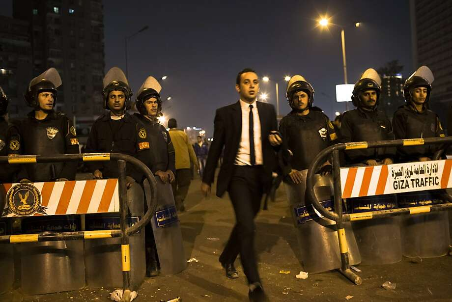 CAIRO, EGYPT - DECEMBER 16: An Egyptian man walks past riot police as they stand guard in front of Dokki police station on December 16, 2012 in Cairo, Egypt. Egyptian police were on high alert after news of a planned protest by Salafist supporters of Hazem Abu Ismail, after an attack on WAFD party headquarters last night on election day. The protest was cancelled after an announcement on Hazem Abu Ismail's Facebook account. (Photo by Daniel Berehulak/Getty Images) Photo: Daniel Berehulak, Getty Images