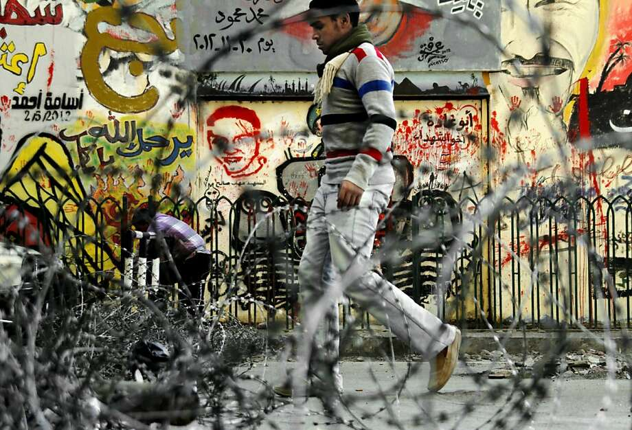 """A man walks near barbed wire set up by protesters in Tahrir Square, the focal point of the Egyptian uprising, in Cairo, Sunday, Dec.16, 2012. Key Egyptian rights groups called Sunday for a repeat of the first round of the constitutional referendum, alleging the vote was marred by widespread violations. Islamists who back the disputed charter claimed they were in the lead with a majority of """"yes"""" votes. (AP Photo/Amr Nabil) Photo: Amr Nabil, Associated Press"""