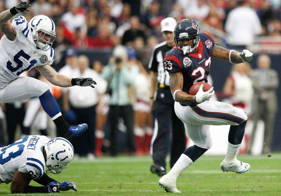 Texans running back Arian Foster (23) breaks away from Colts linebackers Pat Angerer (51) and Dwight Freeney (93) during the first quarter. (Brett Coomer / Houston Chronicle)