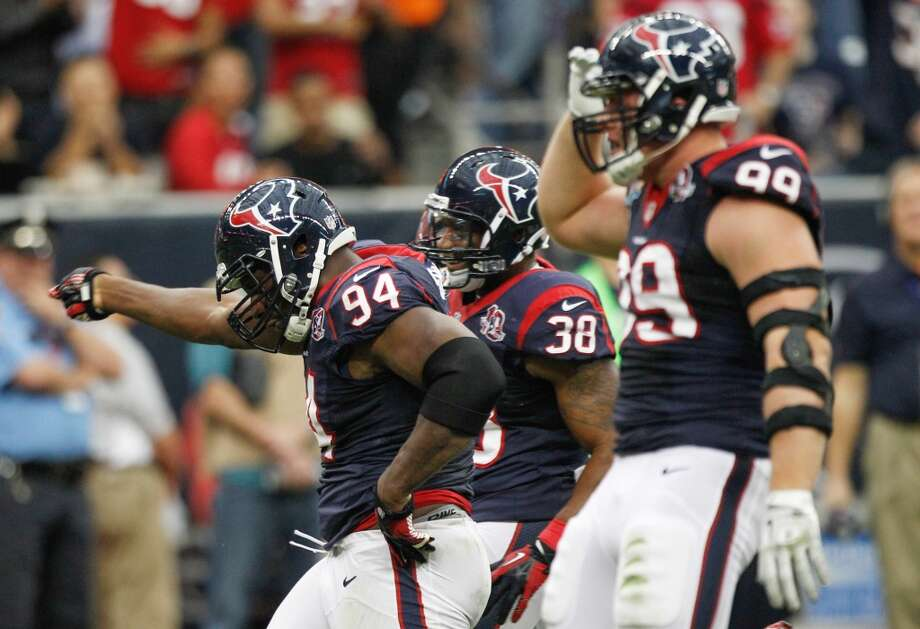 Texans defensive end Antonio Smith (94) and defensive end J.J. Watt (99) celebrate a sack of Colts quarterback Andrew Luck during the first quarter. (Brett Coomer / Houston Chronicle)