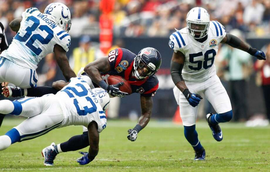 Texans wide receiver Andre Johnson (80) makes a catch between Colts defensive backs Cassius Vaughn (32), Vontae Davis (23) and Moise Fokou (58) during the second quarter. (Brett Coomer / Houston Chronicle)