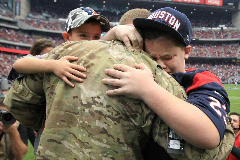 Army Chief Warrant Officer Eric Spoerle hugs his sons, Tristin, 12, right, and Brandon, 6, after he surprised them present during halftime. (Karen Warren / Houston Chronicle)